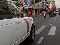 Xe Range Rover di chuyển tại Sài thành trong chiều mùng 2 Tết sử dụng gương của xe máy